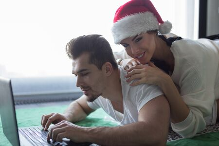 Happy young casucasian couple online shopping on carpet for Christmas Stock Photo