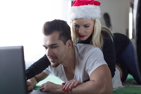Young woman in Christmas hat with boyfriend at laptop online shopping Stock Photo