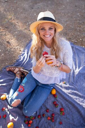 Happy young blonde woman at picnic eating strawberry in nature