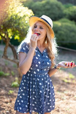 Happy young blonde Caucasian woman in hat eating strawberry outside
