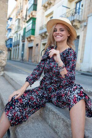 Positive Mediterranean urban blonde woman sitting on stairs, Valletta, Malta