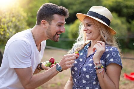 Young man joking with girlfriend on picnic in nature