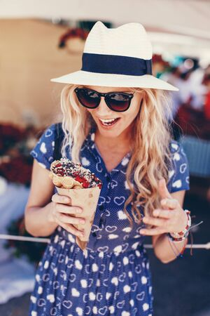 Young blonde woman in hat holding bubble waffle at strawberry festival Imagens