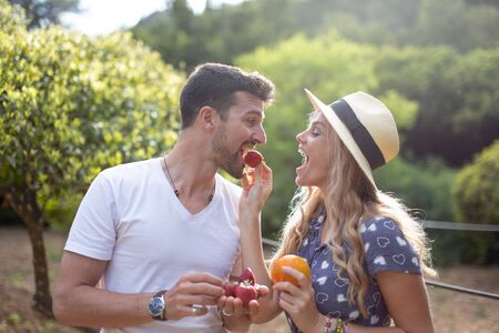 Young woman feeding boyfriend with strawberry in nature on picnic