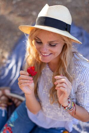20s blonde woman at picnic holding delicious strawberry, eyes closed