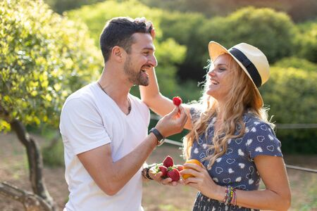 Happy young vivacious Caucasian couple laughing on picnic in nature