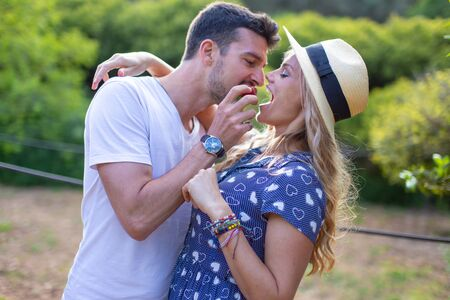 Young man in love feeding blonde girlfriend with strawberry in picnic outdoors