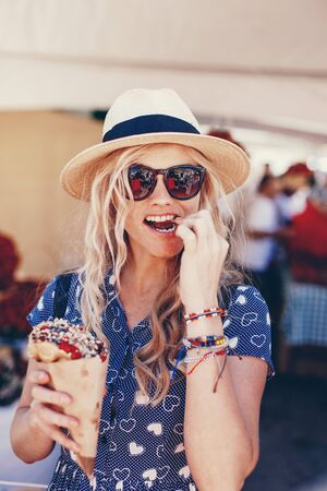 Young blonde woman in hat eating bubble waffle at strawberry festival