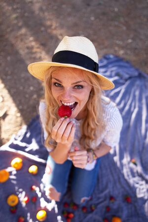 Happy young blonde woman at picnic biting into strawberry Imagens