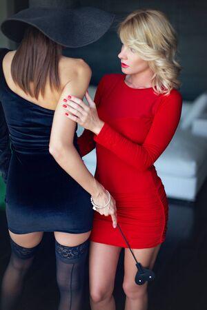 Mujer rubia en rojo con amante por látigo, seducción