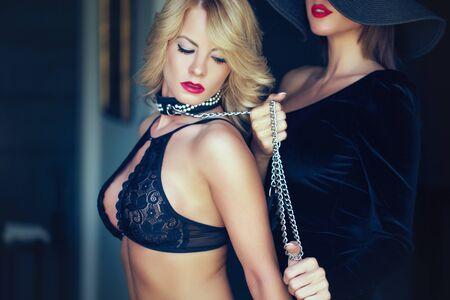 Mujer rubia pecadora en sujetador sostenido por amante en cadena