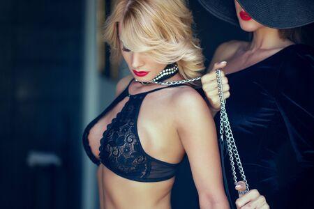 Sensuele blonde verlegen vrouw in beha vastgehouden door minnaar aan ketting