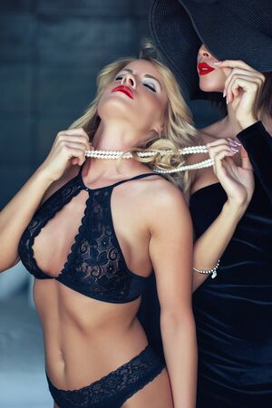 Sensual blonde woman in bra holded by lesbian lover on pearls sin Zdjęcie Seryjne