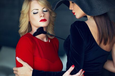 Blonde woman in red with lesbian lover foreplay by whip portrait, eyes closed