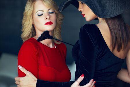 Mujer rubia en rojo con amante por retrato de látigo, ojos cerrados Foto de archivo