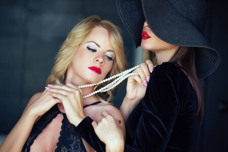 Sensual blonde woman in bra holded by lesbian lover on pearls portrait