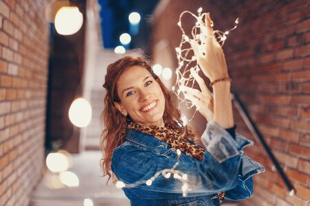 Happy young woman playing with fairy lights outdoors in city, toothy smile