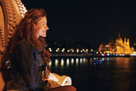 Happy young redhead woman wondering in Budapest night panorama, Hungary