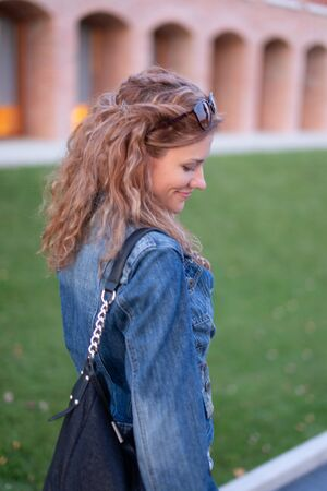 Shy redhead woman side view in park outdoors Banque d'images