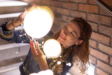 Young Caucasian woman playing with fairy lights outdoors