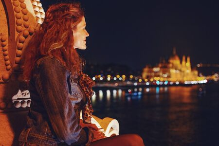 Young 20s redhead woman wondering in Budapest night panorama, Hungary