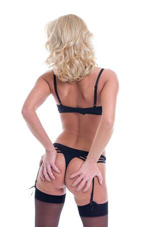 Sexy blonde lustful woman in black underwear grab ass, rear view, isolated on white Standard-Bild