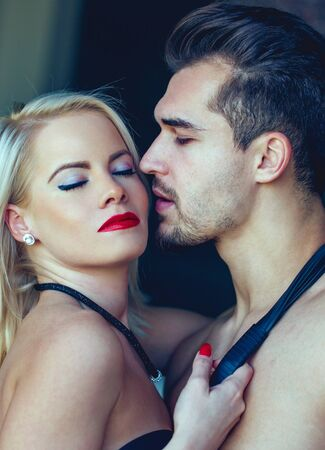 Tempting blonde woman with red lips hoding naked man by tie portrait
