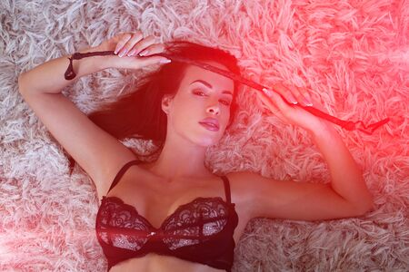 Lustful brunette woman in bra lying on carpet and holding whip in red light