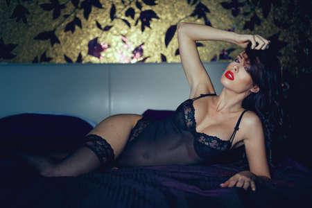 Tempting woman in underwear posing on bed in bedroom