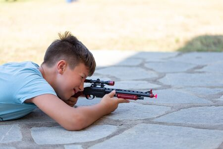 Little Caucasian boy shooting with suction cup toy