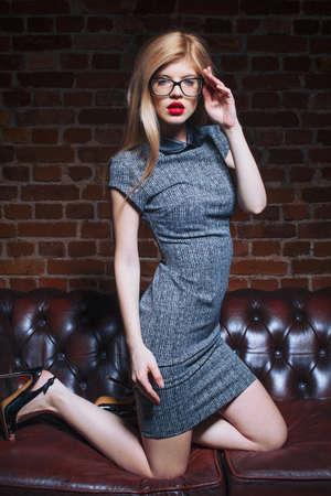 Young sensual blonde woman in eyeglasses posing on sofa at night