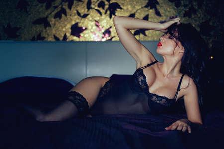 Sexy woman in underwear posing on bed in bedroom