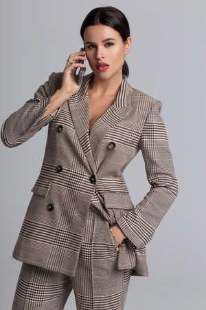 Professional young businesswoman in trendy gray formal wear calling