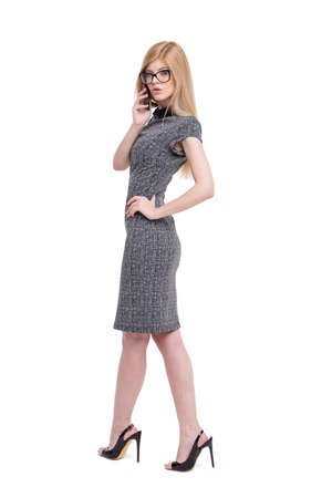 Young blonde businesswoman calling by phone, full body, isolated on white