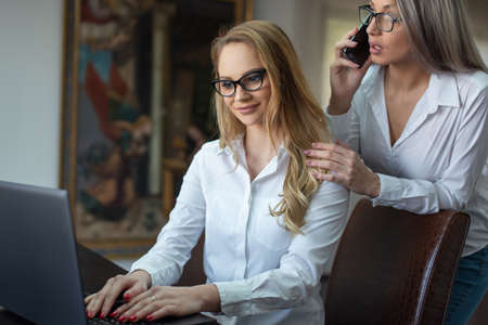 Young white collar busy lesbian businesswomen couple making business, online communication