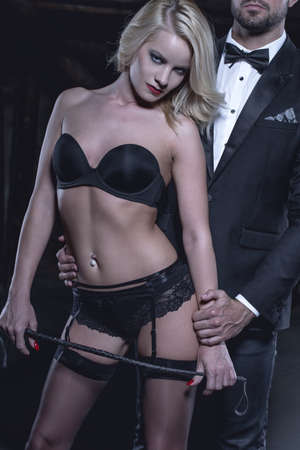 Dominant woman in lingerie with whip holded by rich man concept closeup, bdsm, cinematic style