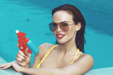 Sexy retro woman shooting with water gun in swimming pool at edge 免版税图像