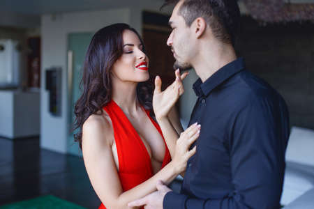 Sexy playful woman in red seducing younger man indoors
