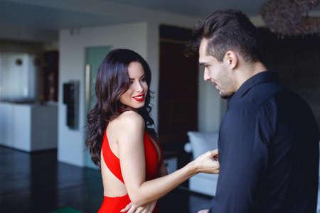 Sexy woman in red flirting seducing younger man indoors 版權商用圖片