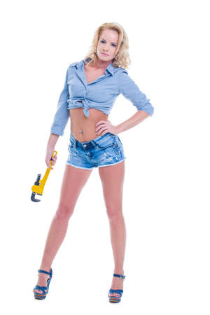 Sexy blonde plumber woman in denim short holding wrench, full body, isolated on white