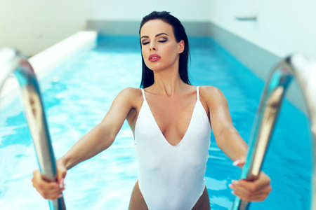 Sensual brunette woman in swimwear get out from swimmig pool at summer eyes closed 免版税图像