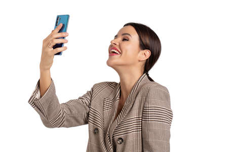 Expressive young woman in gray chequered suit taking selfie, isolated on white