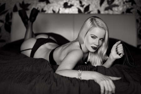Sexy blonde woman in underwear posing on bed in bedroom, black and white