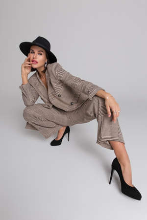 Young fashionable celebrity posing in hat at studio photoshoot