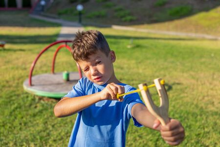 Little kid shooting with slingshot at playground outdoors
