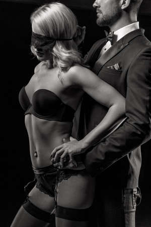 Rich man in tuxedo holdinng sexy woman in underwear at night, bdsm, black and white Standard-Bild