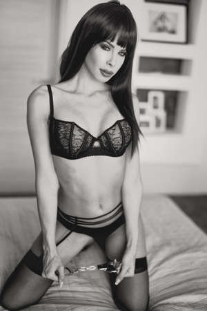 Sexy brunette woman in wig, underwear, and handcuffs posing on bed in bedroom, bdsm, black and white