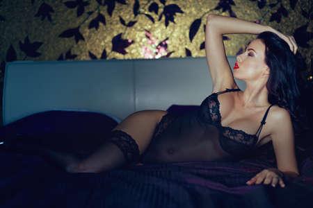 Sensual brunette woman in underwear posing on bed in bedroom