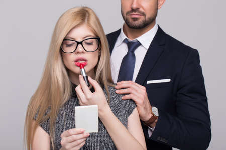 Young femme fatale woman applying red lipstick with mans hand on shoulder 版權商用圖片