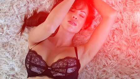 Sexy woman in bra posing on carpet, red light district